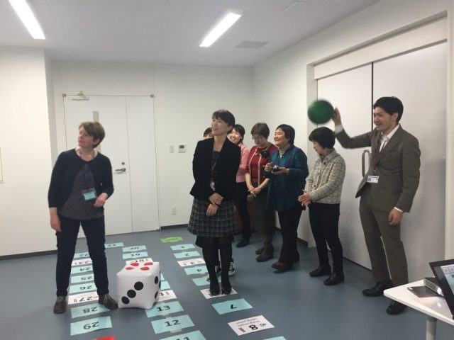 Six adults and one facilitator play a giant version of Snakes & Ladders using a large inflatable dice and coloured floor tiles