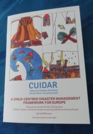 The CUIDAR Framework report front cover. A small white booklet with the 4 CUIDAR logo pictures (clockwise from top left: volcano, earthquake, storm and wave) prominent on the page. Below it are written 'CUIDAR Cultures of Disaster Resilience among children and young people' in blue. Below this are written the words 'A child-centred disaster management framework for Europe. Produced by the EU Horizon 2020 project. CUIDAR: Cultures of Disaster Resilience among Children and Young People. The Twitter handle @CUIDARProject. www.lancaster.ac.uk/cuidar