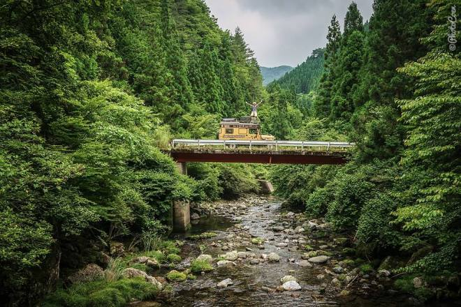 Overlanding in Japan, here: woman standing on the roof of a yellow Land Cruiser that is parked on a bridge surrounded by forest.