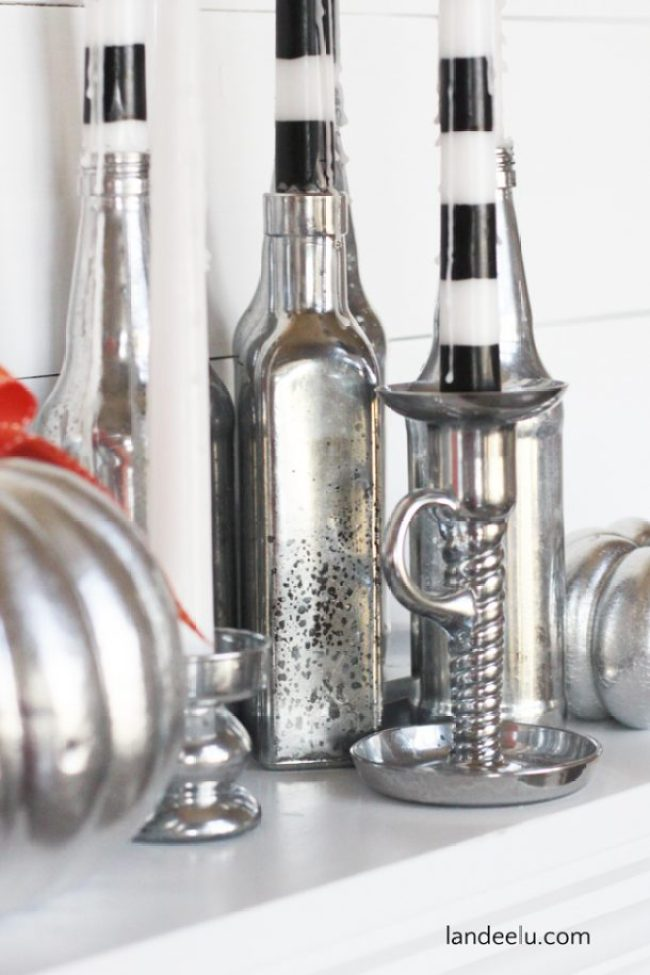 DIY Mercury Glass Halloween Candles | landeelu.com Upcycle some old bottles and glassware into glitzy Halloween candle holders! Love the striped candles too!