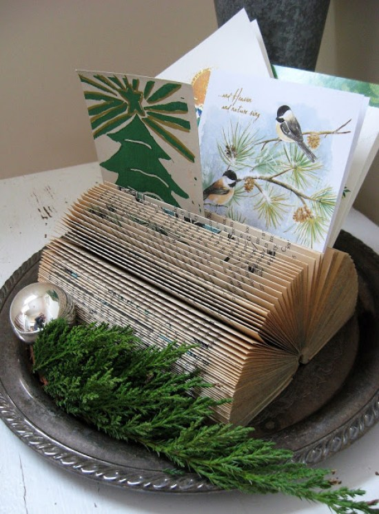 What a fun idea to use an old book to display your Christmas cards! | Four Corners Design