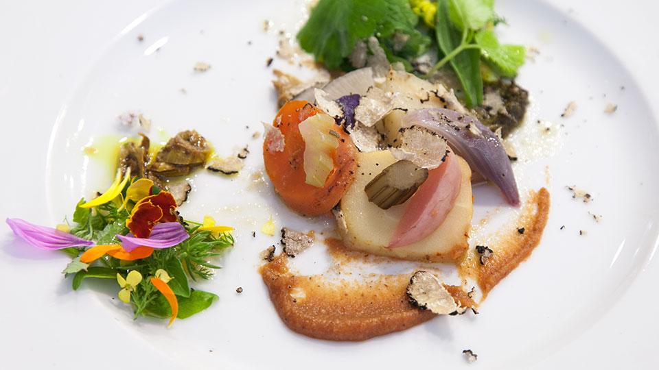 Ein Wildkräuergericht aus dem Restaurant mit Blüten angerichtet