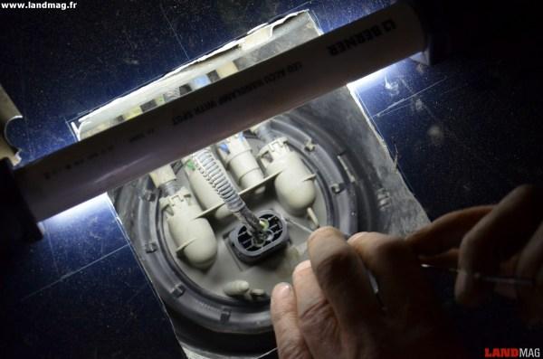 12- Avec une pointe, désengager délicatement les 2 pattes en plastique qui maintiennent la prise électrique et retirer celle-ci.