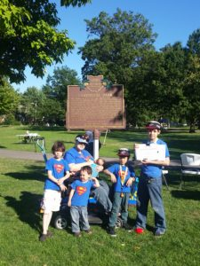 mom in a mobility scooter breastfeeding baby surrounded by four older sons in Superman shirts in front of historic placemark for Lakewood Park