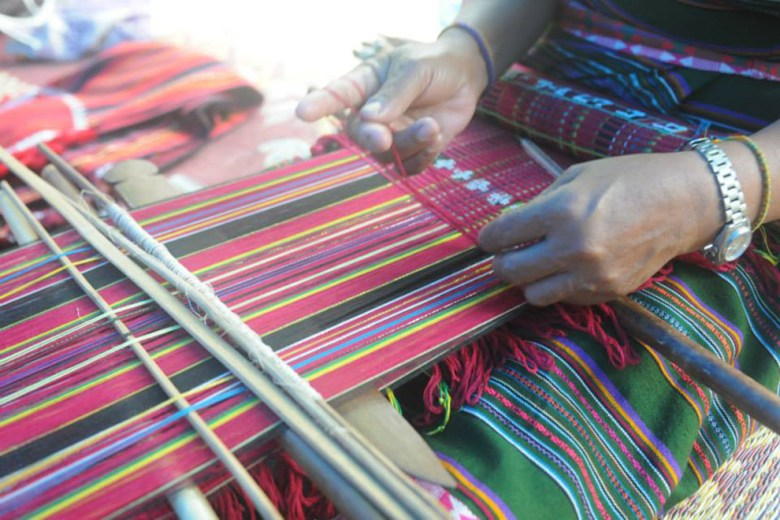 close up of a woman's hands while she weaves