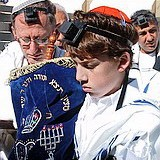 bar mitvah boy wearing Tefillin and carrying Torah at Western Wall in Jerusalem