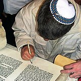 Jewish scribe writing Torah scroll with quill