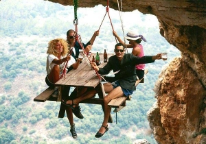 picture of 4 people  hanging on a string a long way up. Accepting a risk.