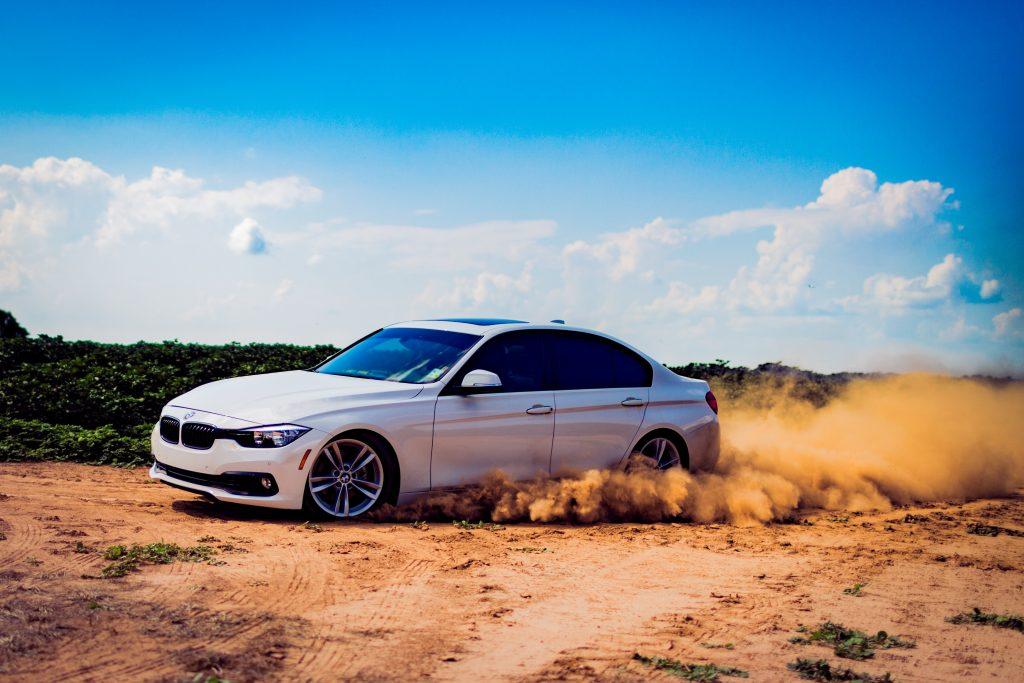 BMW fährt sportlich durch unbewegtes Gelände