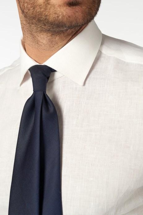 Camicia bianca su misura senza taschino, indossata con cravatta blu