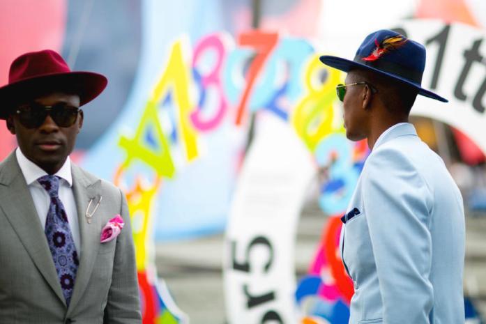 Due uomini indossano un abito su misura grigio (a sinistra) e azzurro (a destra) e borsalino di feltro rosso (a sinistra) e blu (a destra)