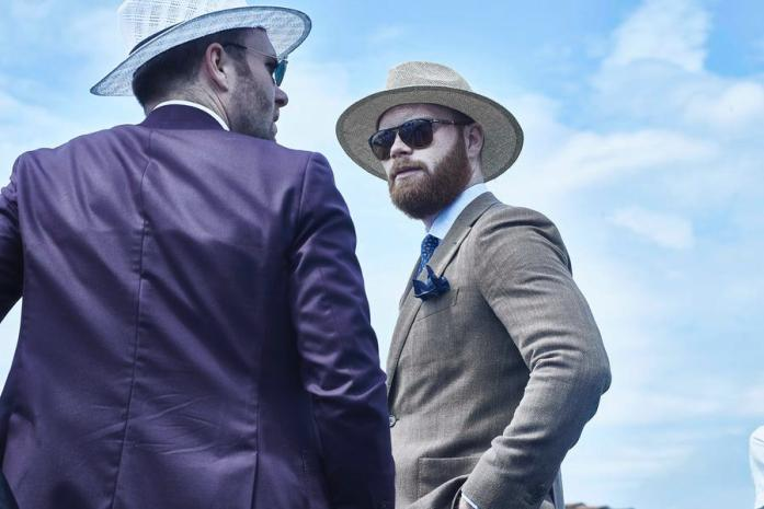 Due uomini dallo stile hipster indossano un abito viola (sinistra) e marrone (destra) e due cappelli di paglietta