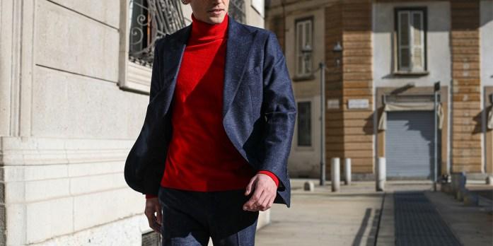Un uomo indossa un completo blu con maglione dolcevita rosso