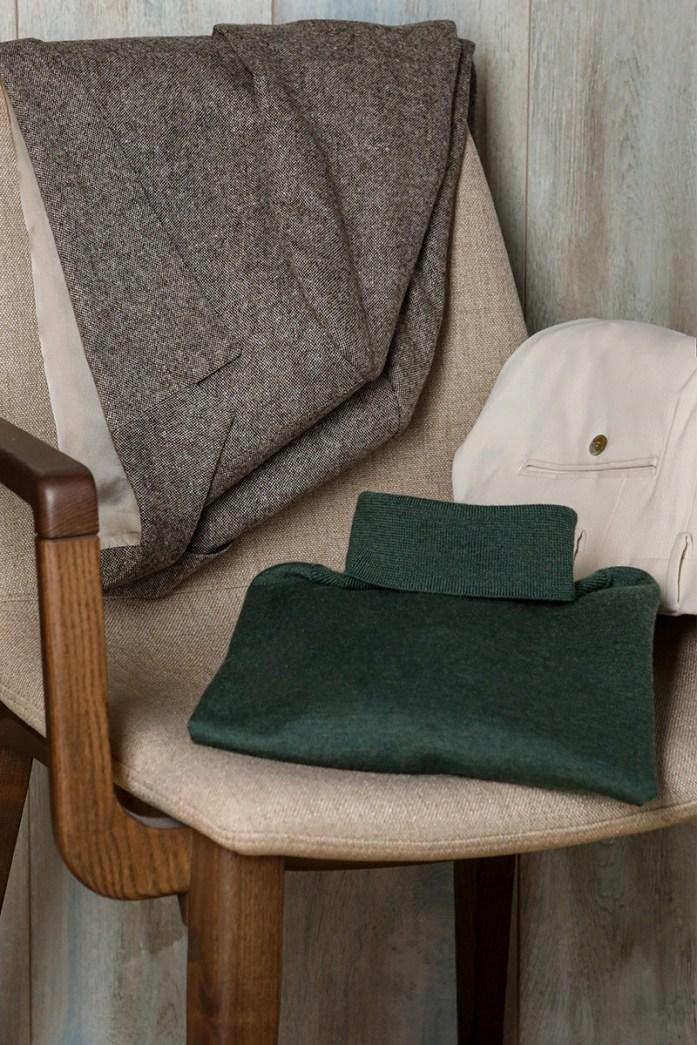 Maglione dolcevita verde, giacca grigia e pantaloni beige appoggiati ad una sedia beige