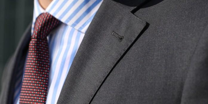 Particolare sul bavero di una giacca, indossata su camicia a righe blu e bianche e una cravatta micropuntinata.