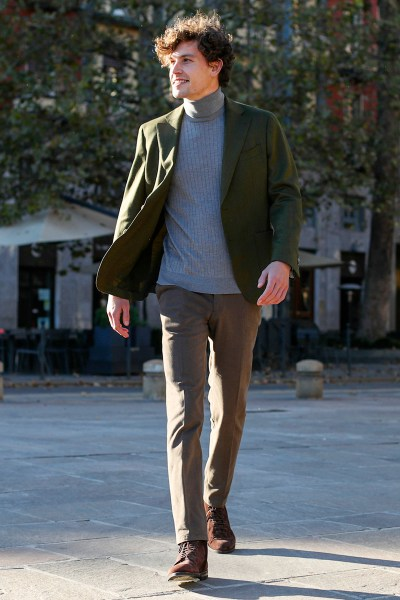 A man wears a green blazer and bespoke brown trousers with a light blue ribbed turtleneck sweater