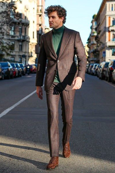 A man wears a tailored brown burgundy jacket and trousers with a green turtleneck sweater