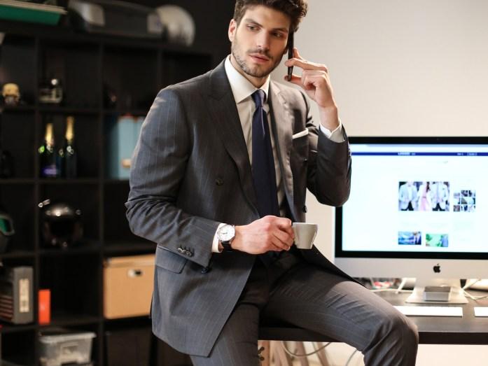 Uomo al telefono, indossa una giacca con completo da ufficio e regge una tazzina di caffè
