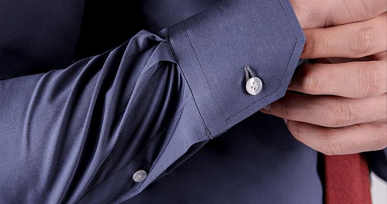 58d391dad104 Dettaglio sul polsino smussato di una camicia blu da uomo su misura in  cotone. Se per ...