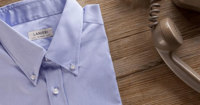 Camicia azzurra Lanieri su misura con colletto button-down ripiegata vicino ad un vecchio telefono anni '70