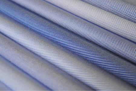 Una serie di pezze di tessuti azzurri per camicia su misura da uomo, di diverse varietà