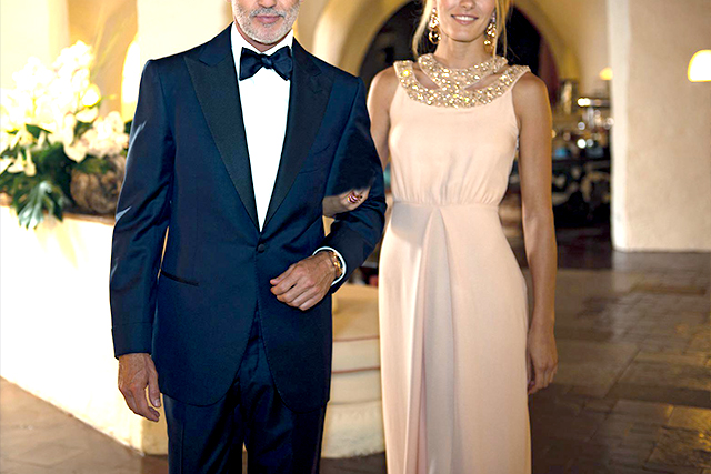 A man wears a blue men's tuxedo with a blue bow tie, accompanied by a woman in a pink dress