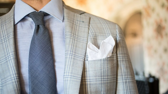 Detail on a Prince of Wales men's jacket, blue shirt, blue tie and white pocket square puff folded