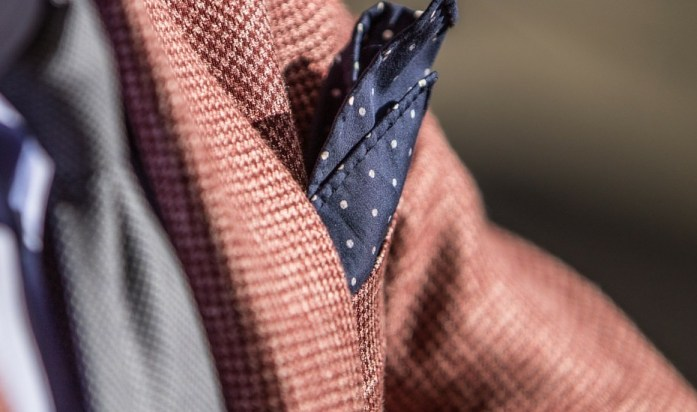 Detail on a blue men's pocket square inserted in the pocket of a brown jacket