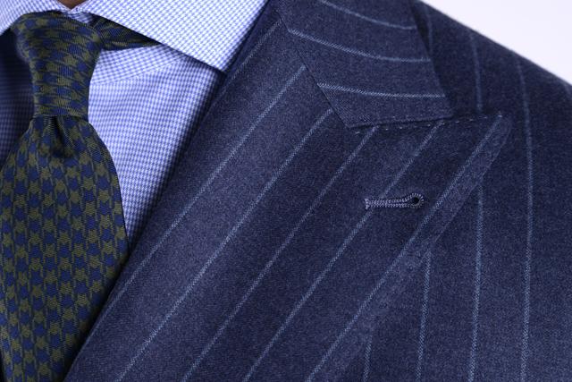 Particolare su revers a lancia di una giacca blu gessato, colletto francese di una camicia a quadri e cravatta verde e blu
