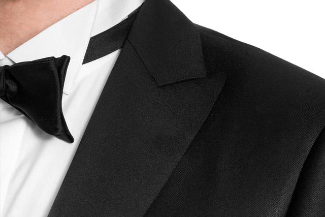Détail sur les revers en pointe d'un smoking, porté avec un nœud papillon noir et une chemise à col diplomate à rabats