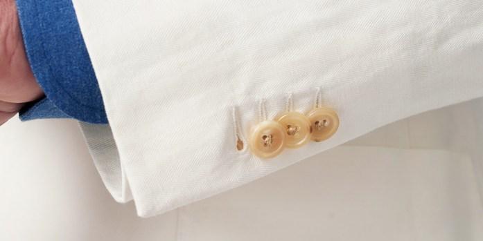 Manica a tre bottoni di una giacca di un abito da matrimonio bianco in lino