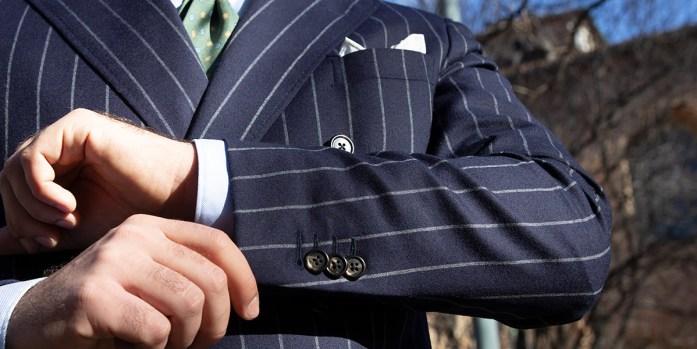 Uomo tocca la manica della giacca di un abito uomo blu gessato