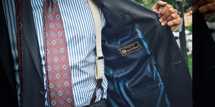 Uomo indossa un completo elegante grigio su misura con tessuto Loro Piana