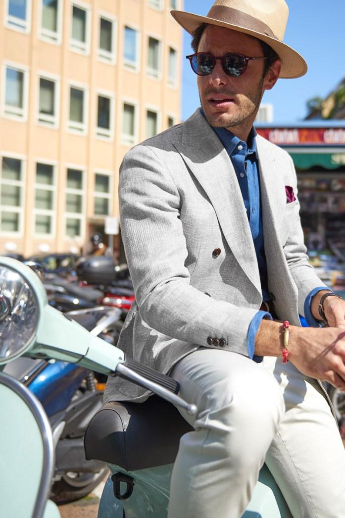 A man wearing a beige blazer while sitting on a Vespa