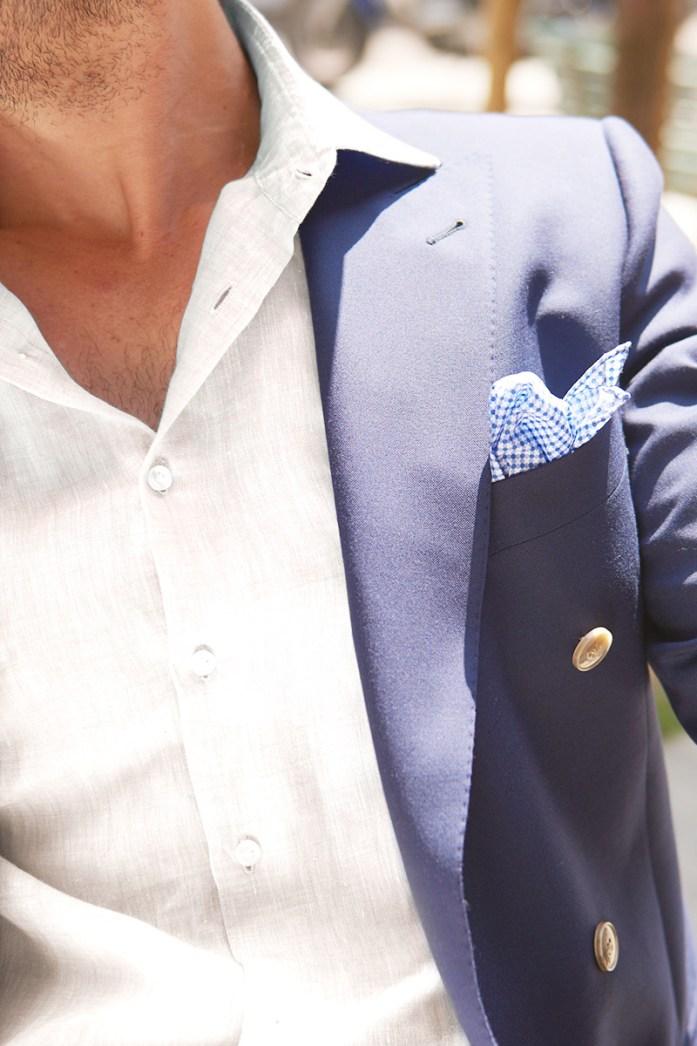 A man wearing a white linen shirt and a blue jacket