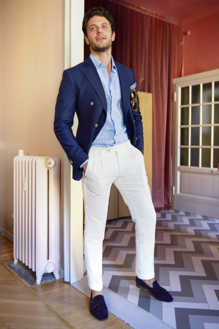 A man wearing white chinos and a blue blazer