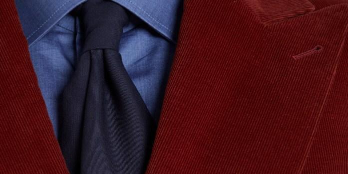 Dettaglio di una giacca in velluto a coste con camicia denim e cravatta blu
