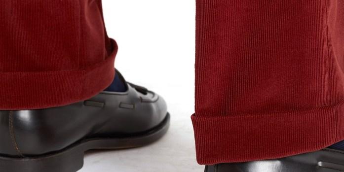 Dettaglio fondo con risvolto di pantaloni in velluto a coste rosso: la lunghezza arriva fino a sfiorare la tomaia della scarpa