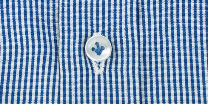 Dettaglio sul bottone di una camicia a righe blu e bianche cucito con filo azzurro.