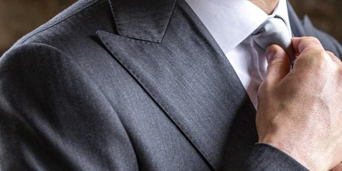 Un uomo sistema il nodo alla cravatta indossata su camicia bianca e abito grigio con revers a lancia