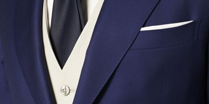 Particolare su un abito blu con gilet panna, cravatta nera, camicia e pochette bianche
