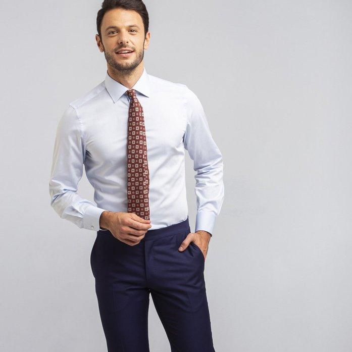 Un uomo indossa una camicia eco azzurra in cotone biologico, cravatta fantasia bordeaux e pantaloni blu.