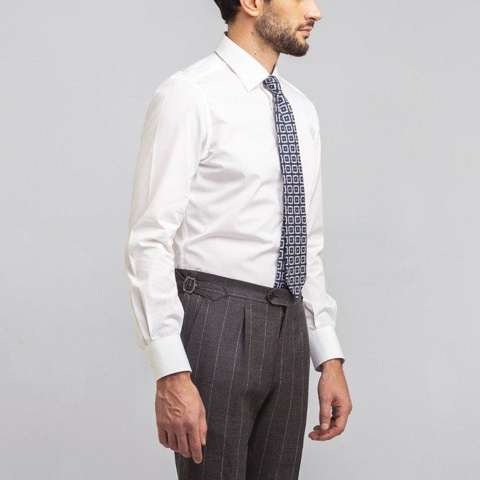 Un uomo indossa una camicia traveller bianca, cravatta fantasia e pantaloni grigi gessati.