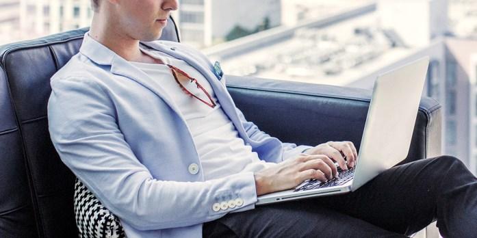 Uomo seduto su una poltrona indossa una t-shirt bianca e un blazer azzurro  mentre lavora d un computer portatile