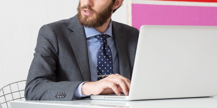 Uomo elegante in giacca, camicia e cravatta davanti ad un computer portatile