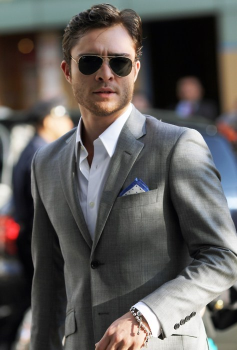 Man with sunglasses wears a gray jacket with one corner up pocket square and white shirt