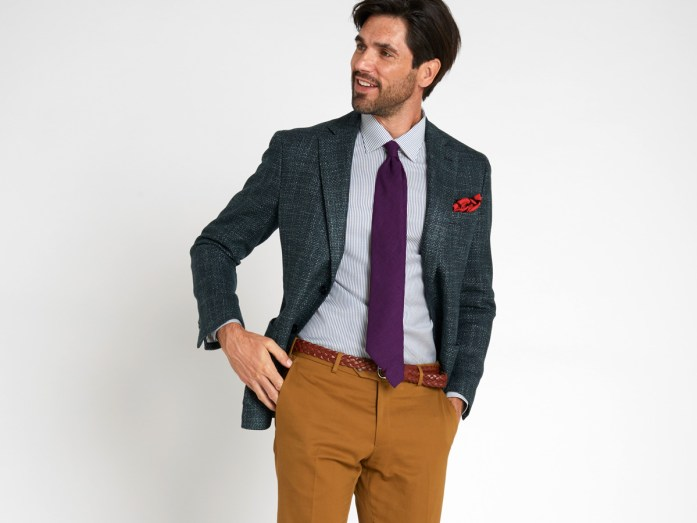 A man wears a broken suit: a dark gray  jacket, a purple tie, a blue shirt, a red pocket square, ocher trousers.