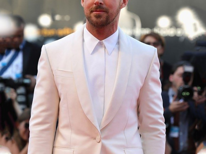 A man wears a white tuxedo, a white shirt without a bow tie