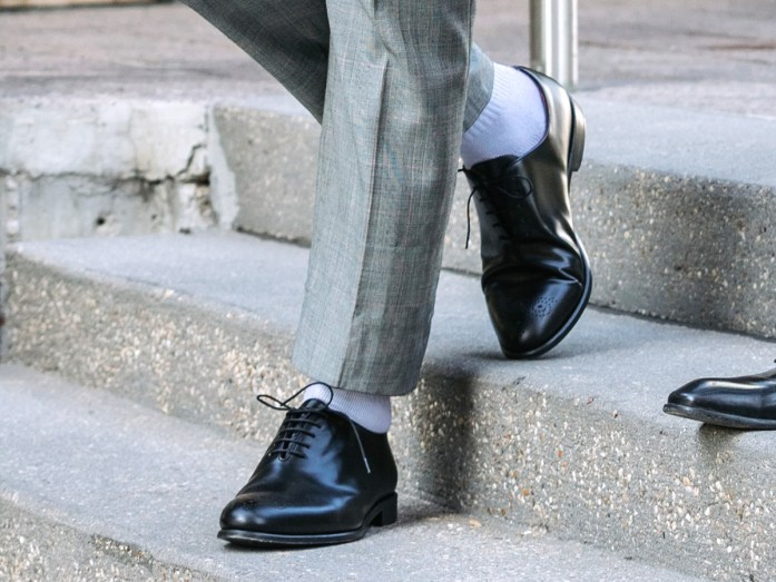 Detail on white socks worn with a pair of elegant black shoes and prince of wales trousers