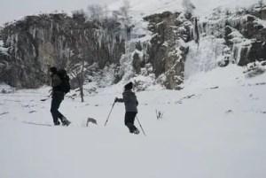 ciaspolatori con una cascata ghiacciata sullo sfondo